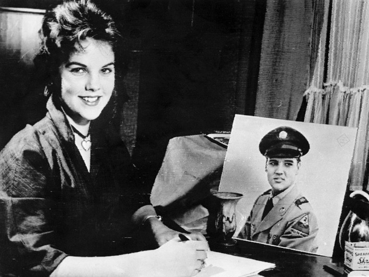 Priscilla Beaulieu Sits Before a Portrait of a Uniformed Elvis Presleu