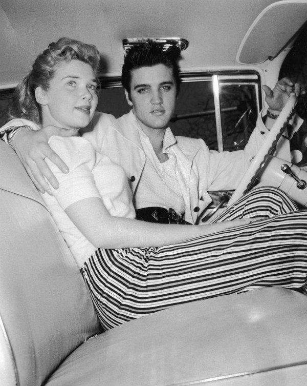 Elvis Presley Sits in the Driver's Seat of a Car with Unidentified Woman